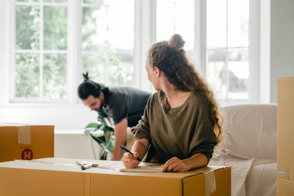Two people with a pile of boxes preparing to relocate
