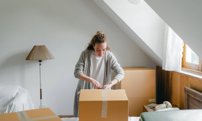 A woman packing a big box in a light living room