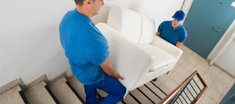 Movers carrying sofa in staircase